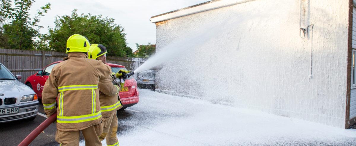 Kent Fire & Rescue firemen spraying building with foam