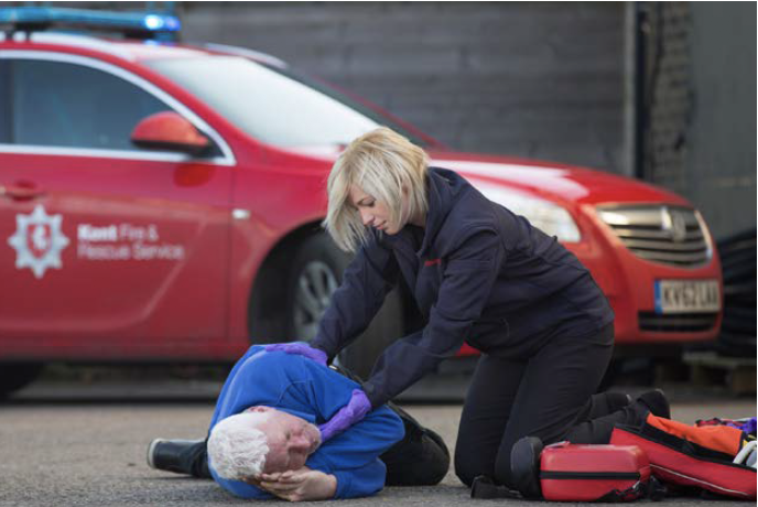 Kent Fire & Rescue fire woman with member of the public teach resuscitation